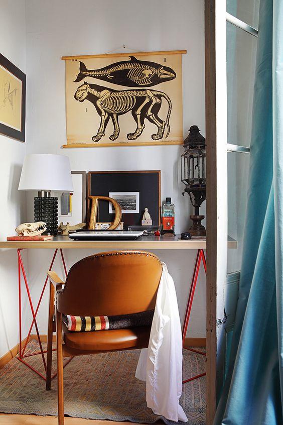 Escritorio en la casa de David Moya. Cartel de zoología sueco de los años 40 de 'Alquián', silla de los 60. Alfombra antigua bereber de Fez y mesa sobre caballetes rojos de los 60. AD España, © Asier Rua