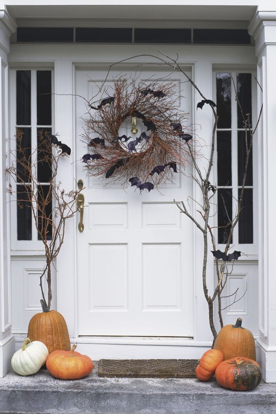 Hang a rustic spooky wreath from your door. Use vines and chic black bats. As simple as that.: