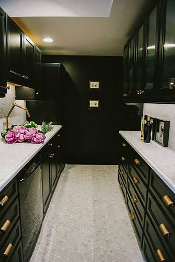 SLAY WITH BLACK IN SMALL, WINDOWLESS SPACES | Narrow galley kitchen with Black cabinets, brass drawer pulls, and white mosaic tile flooring.