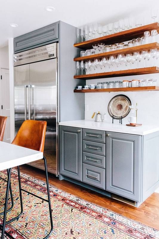 Kitchen with floating shelves filled with glassware, a runner rug, and leather barstools