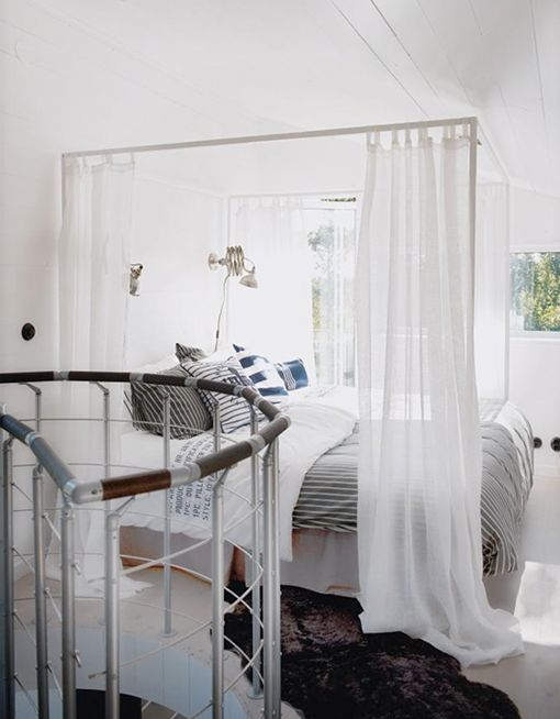 Our Ikea Edlund bed, with sheer white curtains — pretty!