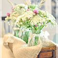 Fresh flowers are a must for the dining table. Roadside flowers are tucked into mason jars that are seated inside a burlap-lined old drawer.