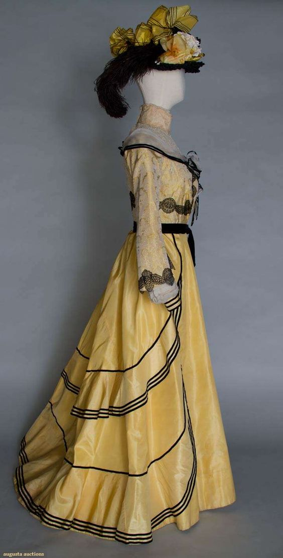 "YELLOW SILK PROMENADE DRESS & HAT, c. 1900    2-piece dress & hat: yellow figured silk bodice, cream lace yoke & high neck, black lace applied bands, white chiffon w/ black velvet ribbon shoulder scarf, yellow silk faille skirt w/ black velvet ribbon trim, black straw hat w/ cloth flowers & silkribbon, B 32"", W 23"", Skirt L 42""-47"", (light stains on skirt, waistband unstitched at CB) very good."