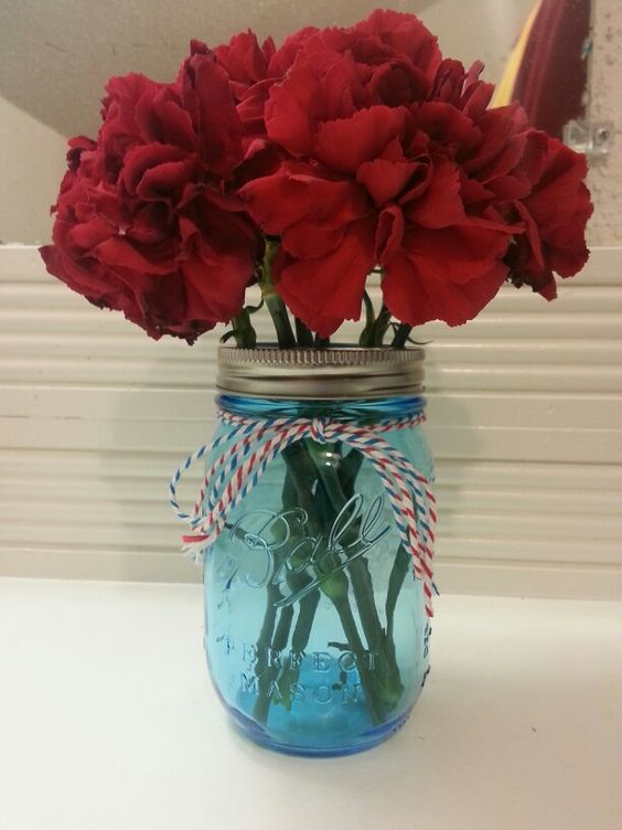 Blue mason jar red carnation centerpiece carnival country