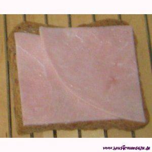 Schinken auf dem Toast Hawai - die runden Scheiben vierteln und dann je 2 Viertel pro Toast legen