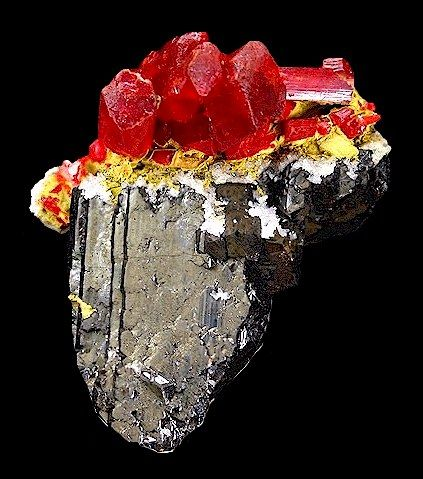 Deep red crystals of Realgar with Orpiment perched atop a crystal of Sphalerite