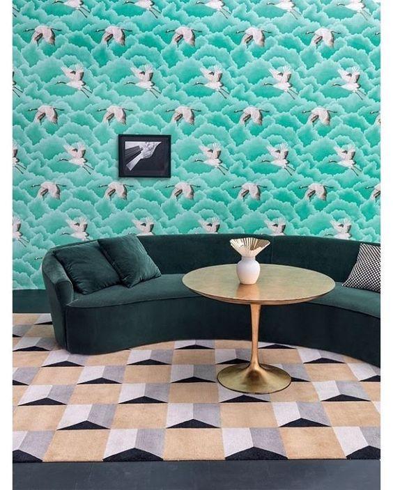 #15salasverdes - Combinações nada óbvias são capazes de revolucionar qualquer ambiente, a exemplo da sala acima. O sofá de veludo verde escuro dialoga com o papel de parede Cranes in Flight, da Harlequin, coberto por nuvens verde-água. Confira mais ambientes com o tom clicando no link da bio ou acompanhe aqui no Instagram 🌿 #casavogue #decoração #interiores #décor #salaverde #verde