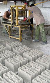 Dos obreros operan máquina de fabricar bloques