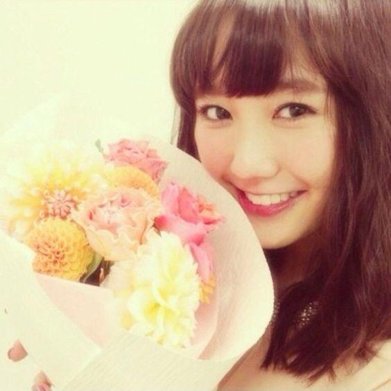 花束を持ち自撮り撮影をしている鈴木友菜