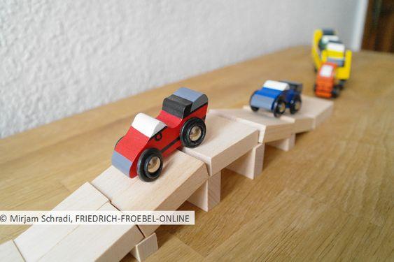 Autos, die über eine Brücke aus Holzbausteinen fahren- so macht Bauen mit Kindern Spaß