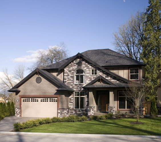 Large two story house with a manicured lawn a combination for Stucco and siding combinations