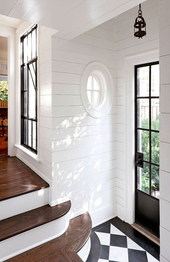 A back hallway is brought into the light with a large window and white-painted wood planking on the walls - Traditional Home®    Photo: Emily Followill: