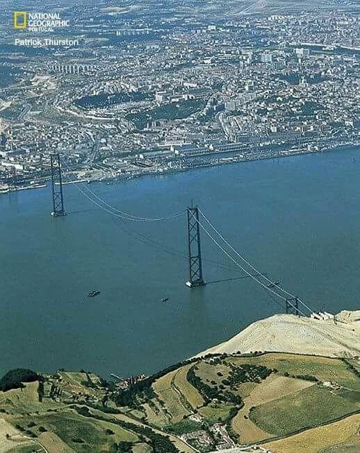 A ponte sobre o Tejo completa hoje 50 anos. Em 1964, uma equipa da National Geographic esteve em reportagem no país. O fotógrafo Patrick Thurston registou este momento memorável. Havia pilares, mas o tabuleiro ainda não fora colocado. #fotoscomhistoria