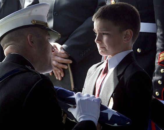 8 year old Christian Golczynski accepting the flag for his father