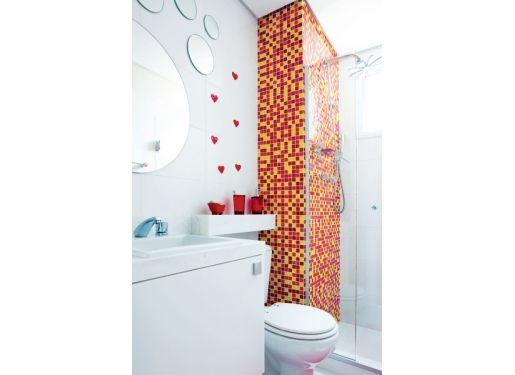 Acima da bacia sanitária, uma prateleira de mármore branco piguês abriga acessórios de acrílico vermelho.