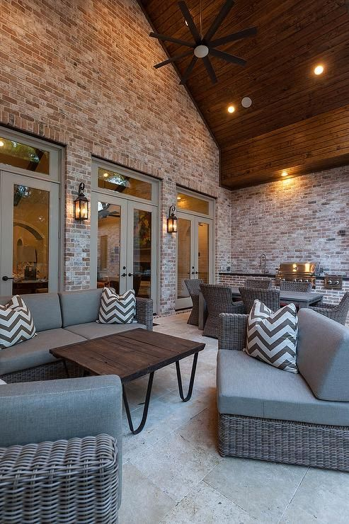 A wall of gray French doors and transom windows open to a covered patio with vaulted ceiling is filled with gray wicker outdoor sofa and chairs and a wood outdoor coffee table.