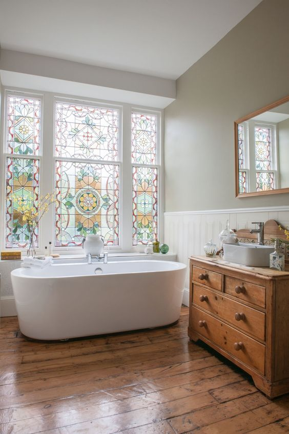 A striking restored Victorian stained glass window in a bathroom renovation