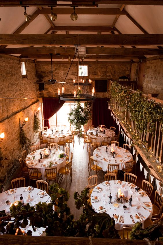 Stunning rustic barn with candles, plant details and large tables. Perfect for the reception, with a warm autumn/winter feel.