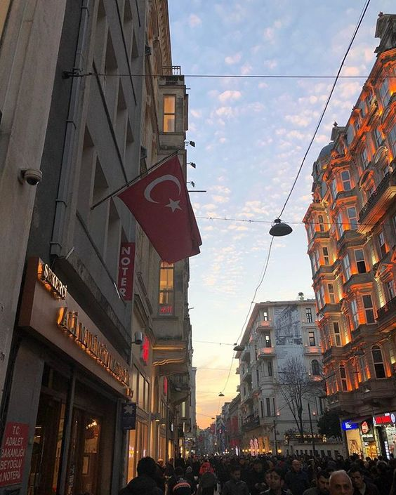 rua de compras de istambul. na foto, bandeira da turquia aparece pendurada em um prédio e o céu está azul