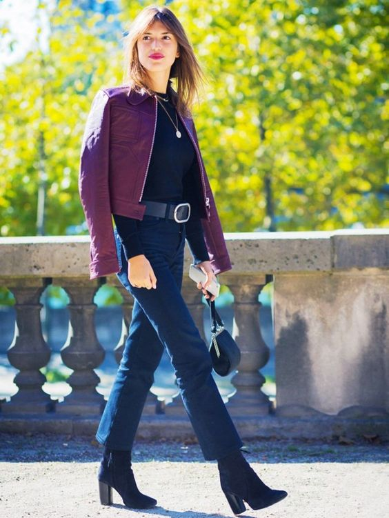 Jeanne Damas wears a black sweater, thick belt, cropped jeans, burgundy leather jacket, and black boots