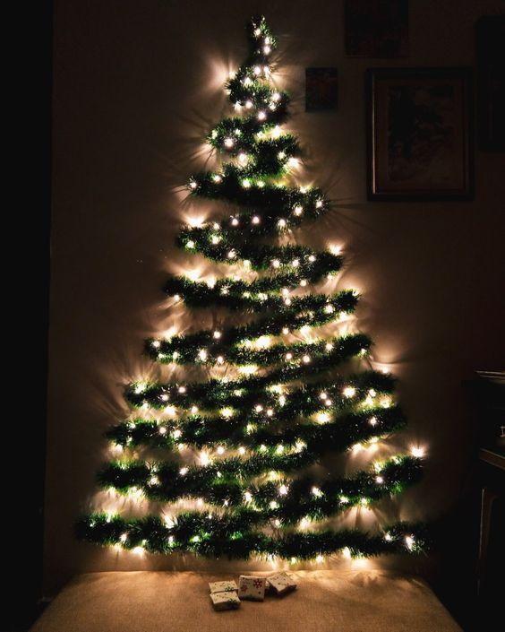 Árbol de navidad creativo, hecho sobre la pared. Se hace sobre la base de un triángulo para tener la proporción y se acomoda una cinta de navidad derecha, y la siguiente en diagonal y así hasta llegar a la cima. Se sostiene con puntillas