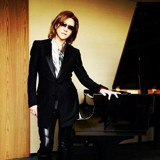 黒い衣装を着てピアノの前に立っているXJAPAN・YOSHIKIの画像
