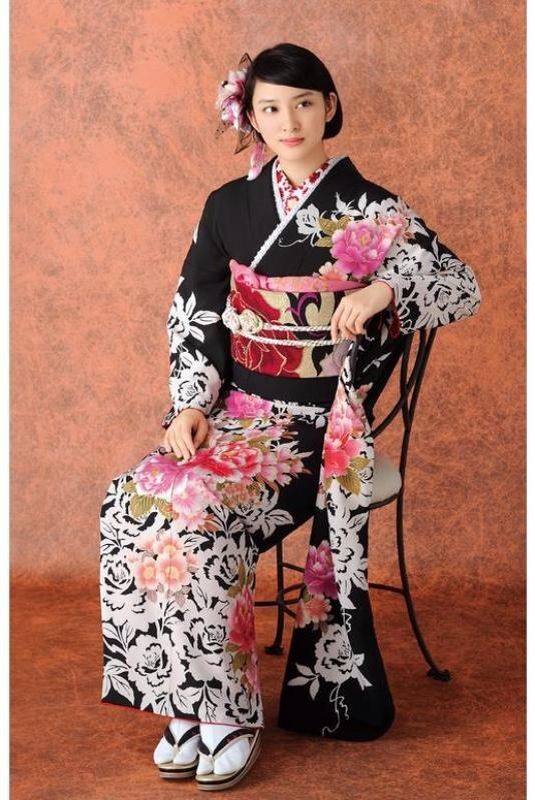 椅子に座っている黒い振袖を着ている武井咲