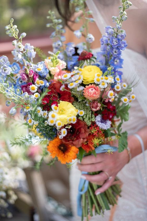 Colorful spring wildflower bridal bouquet at the Spirit of the Suwannee Music Park. Ranunculus, daisies, blue delphinium and fragrant herbs inspired this 70's themed bridal bouquet. Lindsey Leigh Photography.
