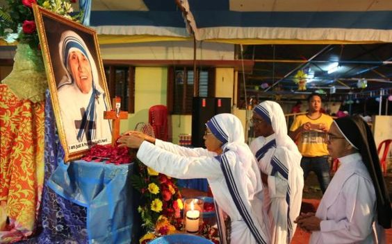 Nuns pay tributes in front of a portrait of Mother Teresa at the Mother House on…