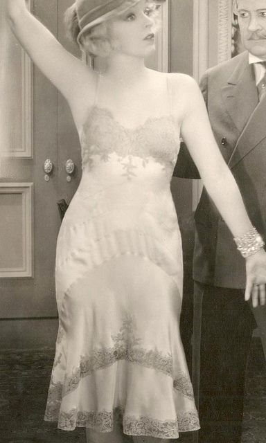 1920's. A lady is showing her dress, the picture shows the type of clothes women would wear in the early 20's. I found it surprising that she is showing so much skin in the time period.