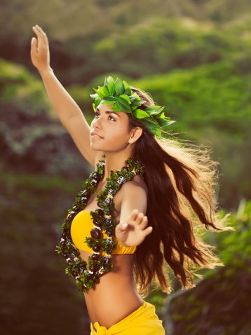 Young Hula Dancer posing for the camera with her hands in the air,...