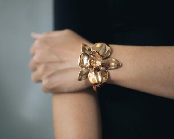 Nuestra floración orquídea escultórica hace un brazalete declaración perfecta. Con una flor única, simétrica montada en un brazalete elegante y