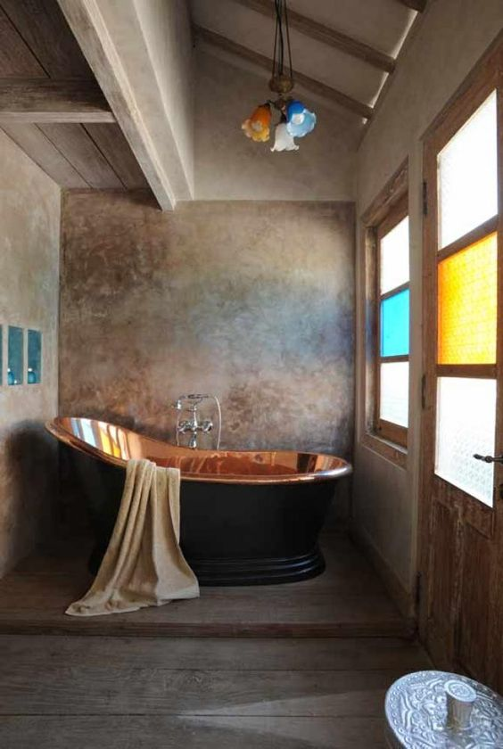 Copper bathtub in a wonderful rustic room. The colored glass on the lights and windows adds to the ambiance.