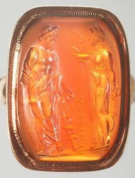 An ancient Roman carnelian gem, 60-50 BC, in a modern setting; depicted on the gem are the gods Asklepios and Hygieia, gods of healing and hygiene; he holds his attribute, a snake-entwined staff. (Kunsthistorisches Museum Vienna)
