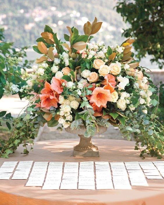 The escort-card table was topped with an abundant arrangement that echoed the lush lakeside surroundings. It included soft coral amaryllis, finesse roses, lydia spray roses, eucalyptus, ivy, olive branches, and two-toned magnolia leaves.