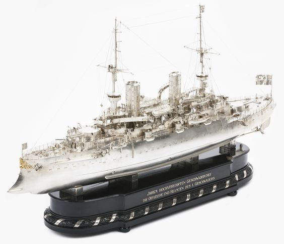 A German Imperial silver model of the warship Kaiser Friedrich III, M. Fadderjahn (Silberwarenfabrik), Berlin, circa 1903 executed in fine detail with imperial flags, geared masts, ship's cannons and deck guns, lights, life boats, propellers etc., with a gilt crest at the bow incorporating a bust of Emperor Friedrich III, the stern on both sides with gilt crowned W-monogram and the ship's name, the carved ebony and ebonised base with dedication