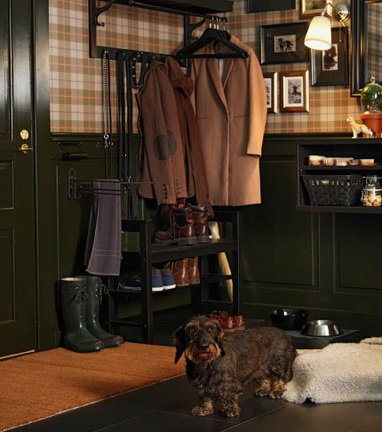 犬が自分のベッドの横で立っている、伝統的なスタイルの玄関。コートが、壁に取り付けられた帽子用ラックに掛っている。ミラーと犬の写真がチェック柄の壁に飾られていて、手間にアームチェアが置いてある。壁の下の部分の木製パネル壁にダブルシェルフが取り付けられている。