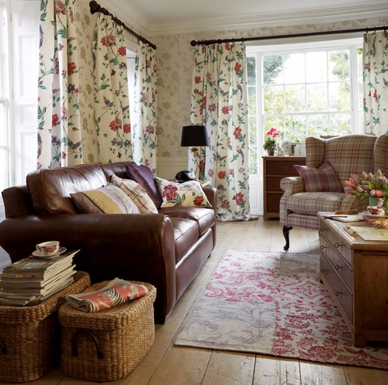 laura ashley  ♥ the mix of leather, baskets, modern florals, print rug, wood floor.