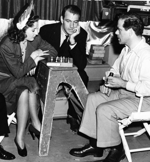 Barbara Stanwyck and Frank Capra playing chess on the set of Meet John Doe (1941) while Gary Cooper looks on