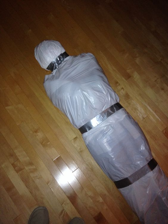 DIY corpse in a body bag, made out of old clothes stuffed with grocery bags, styrofoam, and bubble wrap, then wrapped in white garbage bags and duct tape. Such an easy halloween prop.