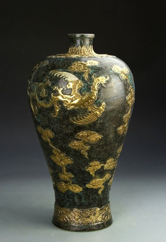 Chinese Gilt Black Glazed Meiping Vase with a wide shoulder, and narrow neck, with a phoenix, clouds, and stylized waves highlighted in relief. Height 18 in.