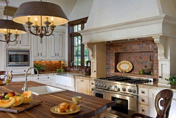 Brick is a timeless material with a homey, vintage feel. The warmth of this brick backsplash emulates the hearth-like stove with its massive hood cover. The rich color tones work to blend the cream cabinetry with the dark wood trim. See more of this home on Porch.com. - CountryLiving.com #diykitchenbacksplash