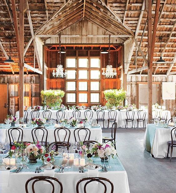 A barn reception doesn't mean everything has to look super rustic. We love these colorful centerpieces on the patterned aqua runners. Go ahead and mix it up! : @jesseleake | @alison_events @brownpaperdesign @jennypennywood #marthaweddings