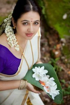 Pretty Girl in a Traditional Kerala Kusavu Saree holding fresh flowers on a banana leaf: