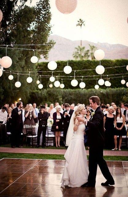Pretty paper lanterns lit up over an outdoor wedding dance for Outdoor dance floor ideas