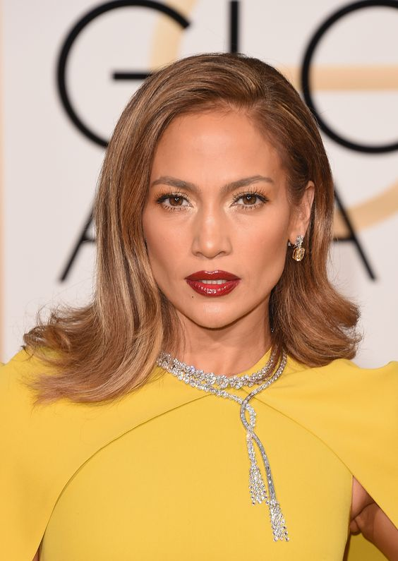 Makeup pro Mary Phillips gave J.Lo glossed gradient lips using three shades of red: Pro-Matte Gloss in Rouge Envy, Nude Allure, and Forbidden Kiss, all by L'Oréal.    - ELLE.com