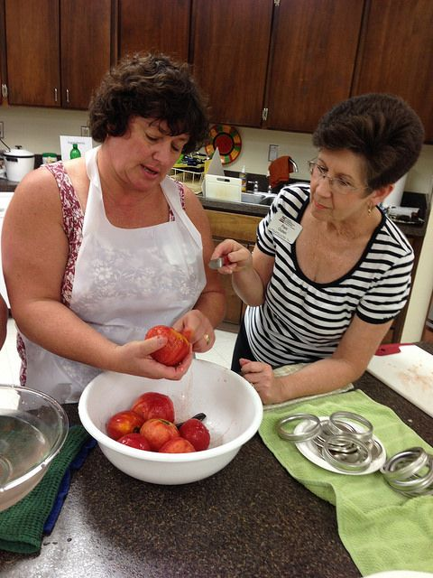 Family and Consumer Sciences agent Pam Outen (right) helps a Cabarrus County participant in the a 2013 tomato canning class. The county Extension food preservation classes have continued to grow each summer and have featured topics such as home pickling, basics of home canning, and freezing and dehydrating. (Robbie Furr photo)
