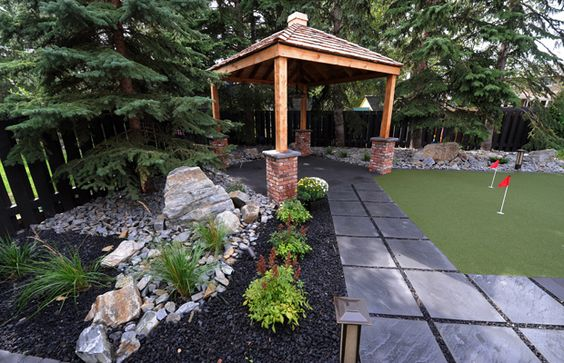 Angus and Heather Watt recast their family backyard as a low-maintenance adult space by installing artificial turf, a putting green, a covered gazebo and an elegant fire table. For full story, click this link http://www.edmontonjournal.com/Extending+backyard+season/10207884/story.html