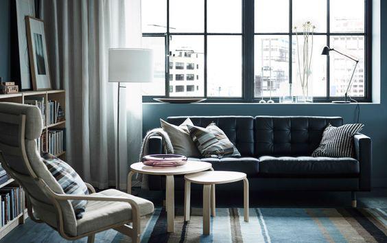Salón con un sofá de piel de dos plazas negro, un sillón con estructura de abedul y un cojín gris, y dos mesas nido de chapa de abedul.
