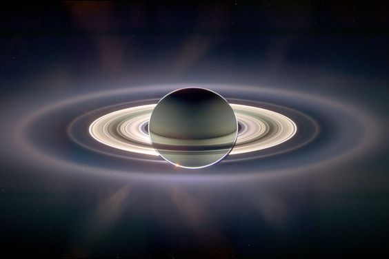 """Saturn, photographed by Cassini. In what some call ""the most stunning photograph ever taken"", the Cassini probe captured Saturn backlit by the Sun. What's more stunning is that Earth is visible in this photo, as a tiny dot just above the rings on the left."""